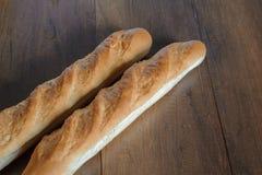 Den franska bagetten bantar den hela kornbagetten på tabellen Royaltyfria Foton