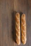 Den franska bagetten bantar den hela kornbagetten på tabellen Arkivbilder