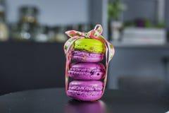 Den franska efterrätten, tre macarons ställde upp knappast bundet med ett härligt band, två violetta och en gröna makron royaltyfria bilder