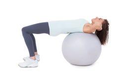 Den färdiga kvinnan som att göra sitter, ups på övningsboll Royaltyfri Bild