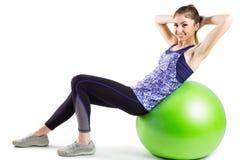 Den färdiga kvinnan som att göra sitter, ups på övningsboll Royaltyfria Bilder