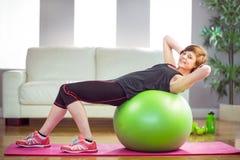 Den färdiga kvinnan som att göra sitter, ups på övningsboll Arkivfoton