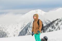 Den freerider Snowboarderflickan står i de snöig bergen i vinter under molnen arkivfoto