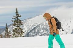 Den freerider Snowboarderflickan står i de snöig bergen i vinter under molnen royaltyfri foto