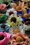 Den frestande ordningen av Bon-bons ställde in i färgrika blommakronblad Royaltyfria Bilder