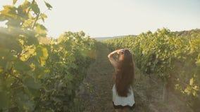 Den fria flickan i klänningen kör längs vingården