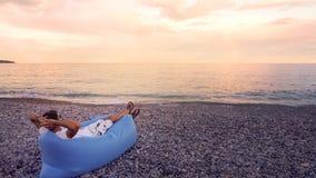 Den fria mannen som kopplar av på stranden och att tycka om seascapesikt och att ha vilar på semester royaltyfri bild