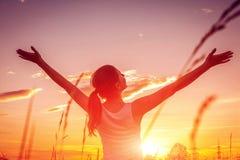Den fria och lyckliga kvinnan lyfter armar mot solnedgånghimlen Harmoni och jämvikt arkivfoton