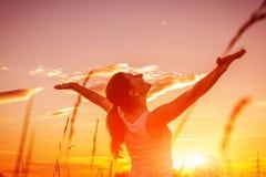 Den fria och lyckliga kvinnan lyfter armar mot solnedg?nghimlen Harmoni och j?mvikt royaltyfri fotografi