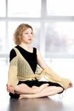 Den fridfulla yogikvinnlign som vilar i kors-lagd benen på ryggen yoga, poserar Arkivbilder