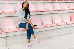 Den fridsamma afro--amerikanen tonåringen lyssnar till musik i hörlurar, medan sitta på de rosa platserna på stadion Fotografering för Bildbyråer