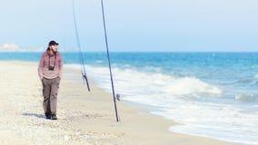 Den fridsamma mannen med en kamera promenerar havskusten på ett soligt Royaltyfri Bild