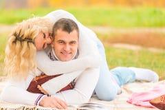 Den förälskade flickan biter av hennes boyfriendbehind Arkivfoto
