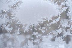 Den frostiga modellen i form av fläcken och härliga spetsiga snöflingor runt om den på vinterfönster förser med rutor Royaltyfria Foton