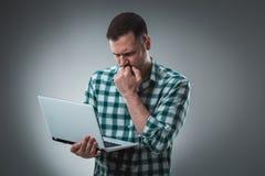 Den frustrerade affärsmannen som rymmer en bärbar dator, täcker hans framsida med hans hand på grå bakgrund Arkivfoton
