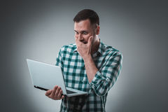 Den frustrerade affärsmannen som rymmer en bärbar dator, täcker hans framsida med hans hand på grå bakgrund Arkivbilder