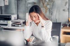 Den frustrerade asiatiska affärskvinnan täcker hennes framsida med hand två och Arkivfoto