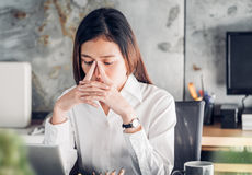 Den frustrerade asiatiska affärskvinnan täcker hennes framsida med hand två och Royaltyfri Bild