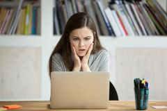 Den frustrerade bekymrade kvinnan ser bärbara datorn som är chockad vid dåliga nyheter Arkivfoton