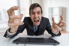 Den frustrerade ilskna affärsmannen är ropa och arbeta med datoren i regeringsställning Royaltyfri Foto