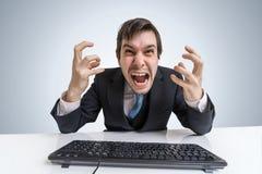 Den frustrerade ilskna affärsmannen arbetar med datoren i regeringsställning Arkivbild