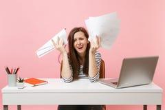Den frustrerade kvinnan i desperation som gråter fördelande pappers- dokument för handhåll, arbetar på projektstund för att sitta royaltyfri bild