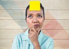 Den frustrerade kvinnan med den klibbiga anmärkningen klibbade på hennes huvud mot träbakgrund Royaltyfria Bilder