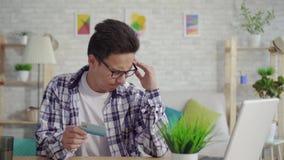 Den frustrerade unga asiatiska mannen i en skjorta skriver in data med en kontokort på en bärbar dator lager videofilmer
