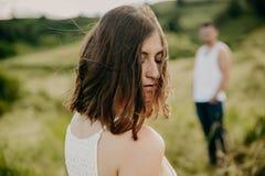 Den frustrerade unga kvinnan som ser i avstånd, tänker om förhållanden som separat sitter med mannen royaltyfri fotografi