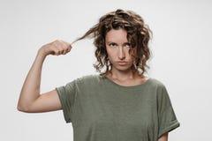 Den frustrerade unga lockiga brunettkvinnan f?r missn?je, rynkar pannan framsidan med missn?je arkivfoton