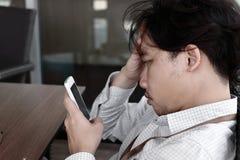 Den frustrerade utmattade asiatiska affärsmannen med händer på pannan som ser mobil, ilar telefonen i hans händer på kontoret Arkivbilder