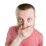 Den förvånade mannen rymmer hans hand över hans skägg Arkivfoton