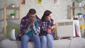 Den fryste unga kvinnan och mannen slogg in i en filt i vardagsrummet värmas bredvid värmeelement lager videofilmer