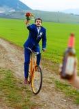 Den fulla brudgummen på en cykel som rymmer en bröllopbukett, jagar en brud med en ölflaska Royaltyfri Foto