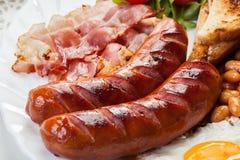 Den fulla engelska frukosten med bacon, korv, stekte ägget och vita bönor i tomatsås Arkivbilder