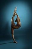 Den fulla längden av den bronzfärgade gymnasten utför på studion