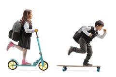 Den fulla längdprofilen sköt av en skolflicka som rider en sparkcykel och ett a Arkivbilder