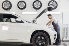 Den fulla längdsidosikten av den undersökande bilmotorn för den manliga mekanikern i reparation shoppar Royaltyfri Bild
