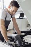 Den fulla längdsidosikten av den undersökande bilmotorn för den manliga mekanikern i reparation shoppar royaltyfri foto