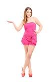 Den fulla längdståenden av en le kvinna som göra en gest med, räcker Royaltyfria Foton