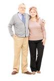 Den fulla längdståenden av en mitt åldrades par i en kram som ser Royaltyfri Fotografi