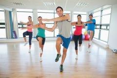 Den fulla längden av konditiongrupp och instruktören som gör pilates, övar Royaltyfria Foton