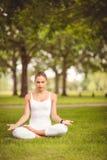 Den fulla längden av kvinnan med stängda ögon, medan sitta i lotusblomma, poserar Fotografering för Bildbyråer