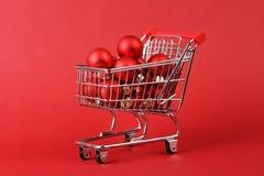 Den fulla shoppingkorgen av röd matt och glansig jul klumpa ihop sig på röd bakgrund Arkivbilder