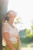 Den fundersama flickan lutar mot tree Arkivbild
