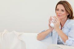 Den fundersama kvinnan med kuper av kaffe på sofaen Arkivfoto