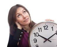 Den fundersama kvinnan tar tid på tid isolerad vit Arkivbild
