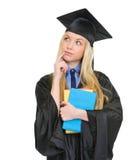 Den fundersama kvinnan i avläggande av examenkappa med bokar Royaltyfria Foton