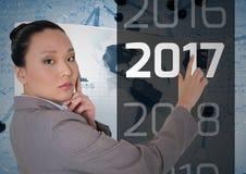 Den fundersamma affärskvinnan som trycker på meddelandet 2017 i 3D frambragte digitalt, bakgrund Royaltyfria Bilder