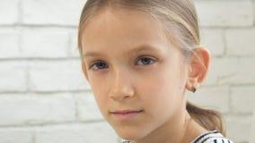 Den fundersamma barnståenden, den eftertänksamma ungeframsidan som in camera ser, blondinen borrade flickan arkivfoton